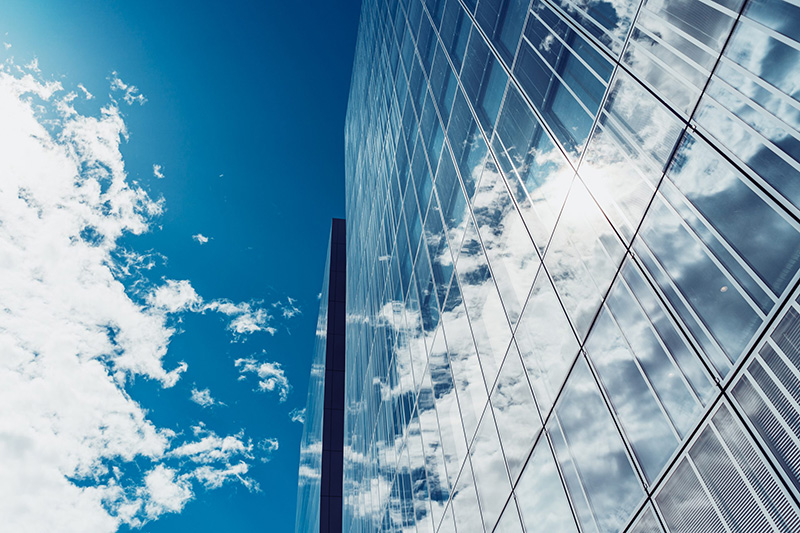 photo en contre plongée d'un gratte-ciel complètement vitré