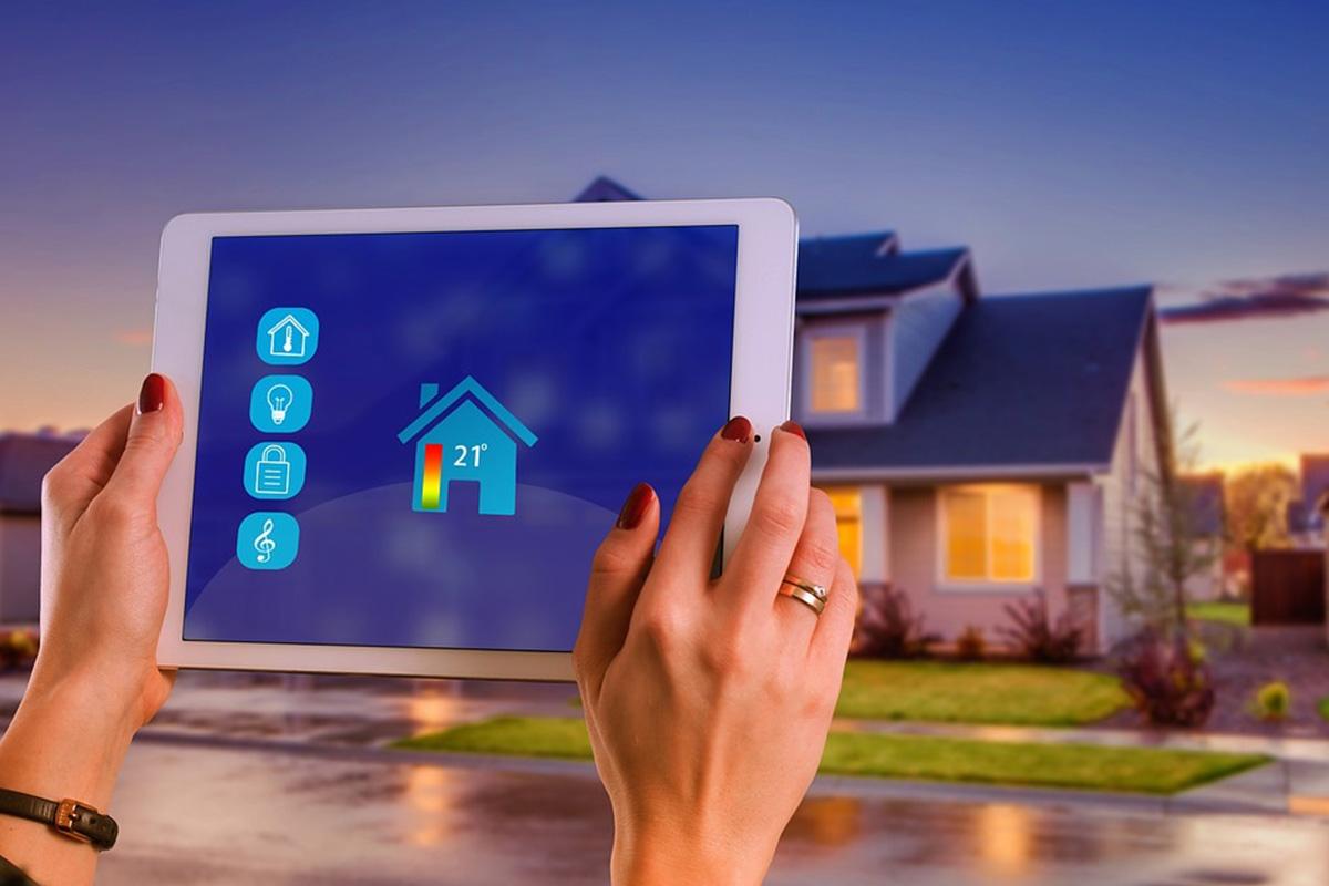 mains manipulant une tablette qui gère les appareils domotiques de la maison en arrière plan